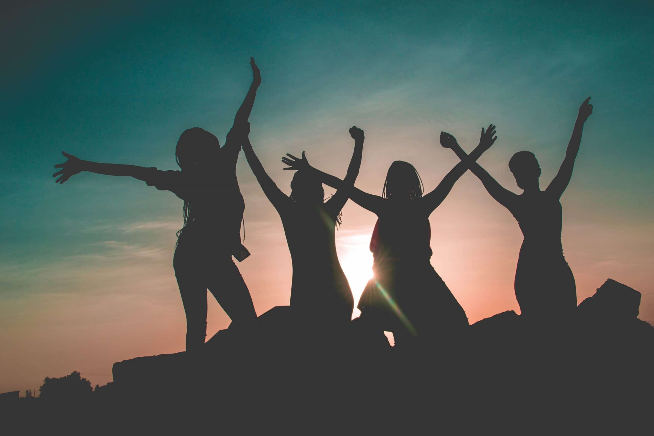 silhouette of four people against sun background 862848 1