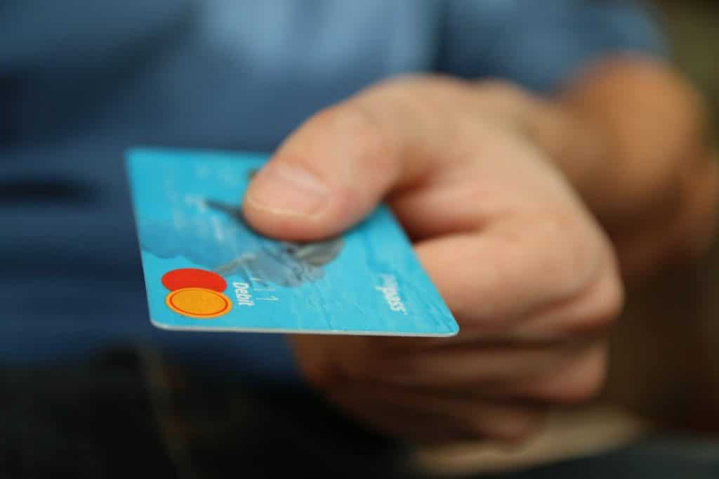 Somebody holding out a credit card with unpaid debt